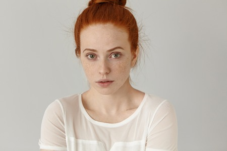 Headshot of attractive young woman of extraordinary appearance looking at camera with shy subtle smile dressed in white blouse. Cute girl with freckled clean skin and green eyes relaxing indoors