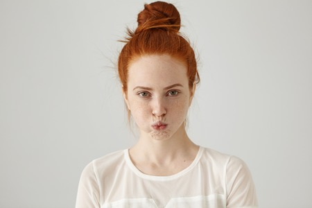 Studio shot of grumpy stubborn young ginger woman with hair knot blowing cheeks and pouting while feeling mad at friends who forgot to invite her to party. Human emotions, feelings, attitude, reaction