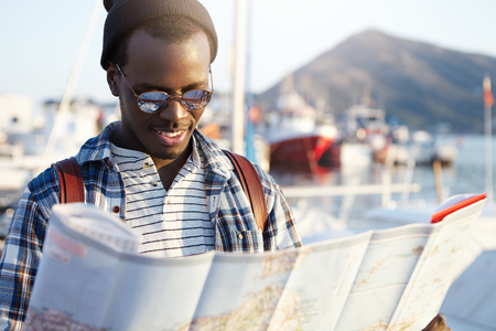 Happy excited dark-skinned man traveler wearing stylish clothing holding city guide in his hands while thinking where to go, sea, mountain and yachts in background. Summer holidays and tourism concept Stockfoto