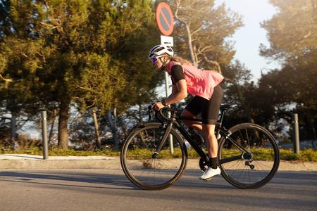 Sport en een gezonde levensstijl. Beeld in motie van Kaukasische vrouw in actieve sportkleding en helm die racefiets in park in ochtendtijd berijden, geconcentreerd en zelfverzekerd tijdens rit kijken