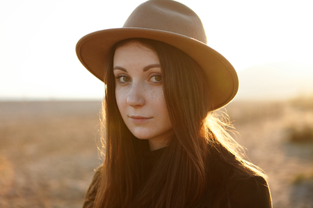 Outdoor close up portrait of tender young romantic woman with magnetic eyes, wearing hat, looking at camera with tranquility and little smile, walking in field, feeling herself in harmony with nature