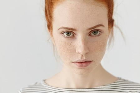 Close-up zeer gedetailleerde foto van mooie charmante jonge vrouw met perfecte gespikkelde huid, gember haar en groene ogen rustig binnen, gekleed in zeeman t-shirt. Tiener meisje poseren in de studio