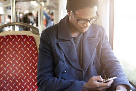 Transport, tourism, road trip and people. Happy cheerful young black man in trendy clothing sitting by window in travel bus, messaging his girlfriend, using smart phone during vacations abroad