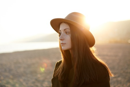 Portrait of pensive and melancholic European girl standing on seacoast in elegant demi-season outdoor clothes, dreaming, reminiscing good and important moments, evening sun kissing top of her head Stockfoto