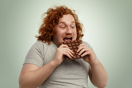 Happy excited young chubby red-haired male opening mouth widely while biting bar of chocolate, feeling impatient. Funny Caucasian man in grey t-shirt consuming unhealthy but delicious junk food Zdjęcie Seryjne