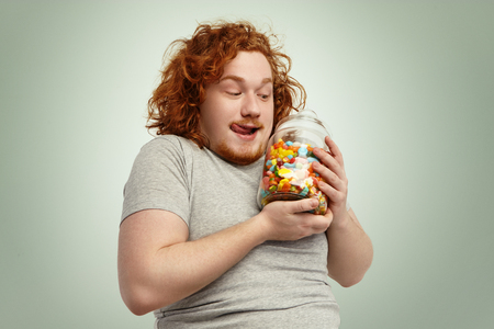 Yummy! Excited funny plump man holding glass jar of sweets and marmalades having anticipated look, licking lips, posing at studio wall. People, food, nutrition, diet, obesity and gluttony concept