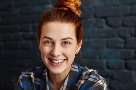 Stylish happy young European girl with ginger hair and charming smile looking at camera with carefree and relaxed expression while having rest at coffee shop, waiting for friends to join her for lunch