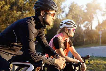 Outdoor image of sporty young European woman and man on bicycles during weekend cycle ride, stopped to admire nature in city park zone, standing in silence, listening to sounds of birds singing