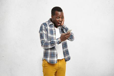 Close up portrait of black shocked hipster in stylish and trendy yellow pants, holding smartphone in one hand touching his head with another, looking scared and confused reading text message or e-mail Stockfoto