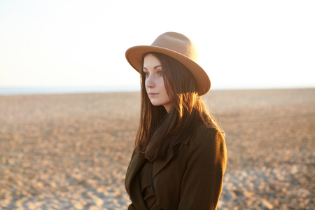 Attractive young European female dressed in stylish overclothes having nice walk along coastline on sunny day, came to the sea for contemplating sunset. Pretty girl in hat relaxing on sandy beach