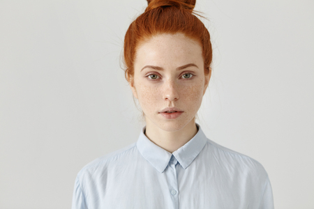 Close up shot of attractive successful young red-haired businesswoman in formal shirt having serious confident look before working day, posing at white office wall. People and lifestyle concept