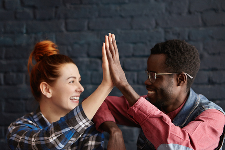 Happy ginger white student girl and her handsome black male group mate in eyeglasses giving high five, congratulating each other while resting at cafe after passing difficult examination at university Stockfoto
