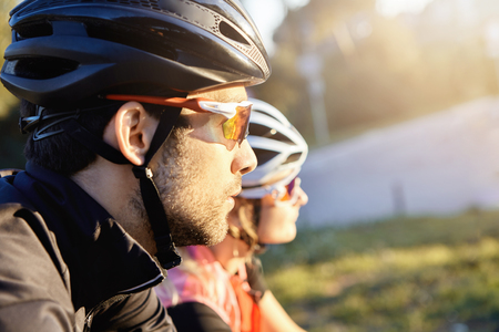 Cropped portrait of two cyclists in helmets and sunglasses looking at something while riding their bicycles in suburban area. Man and woman on racing bikes spending morning hours together before work