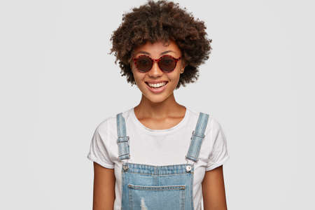 Fashionable dark skinned woman with Afro haircut, wears trendy shades and overalls, smiles gladfully at camera, models against white background. Charming black teenager expresses positiveness