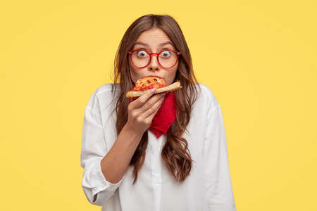 Surprised European fashionable woman has slice of pizza, looks at camera, dressed in oversized shirt, surprised with very nice taste, isolated over yellow background. People and fast food concept