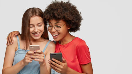 Cheerful mixed race young women watch funny video from social networks, view common photos, have happy facial expressions, hug against white background with free space for your promotion, slogan