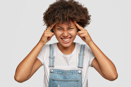 Desperate displeased dark skinned model keeps both index fingers on temples, has headache, suffers from pain, has bad memory, dressed in white t shirt and overalls, models against white background Stock fotó