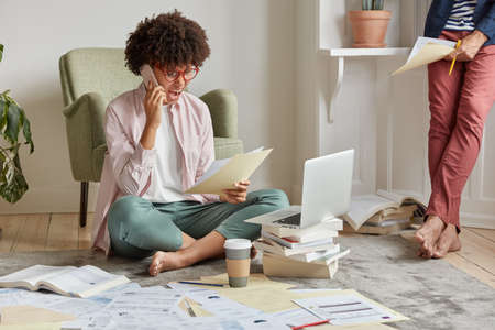 Indoor shot of outraged businesswoman shouts at colleague via cell phone, holds documents, keeps legs crossed, wears transparent glasses, discontent with sales, barefoot guy stands in background