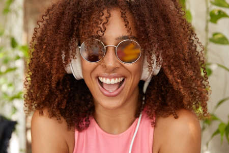 Photo of joyful stylish teenager with Afro haircut, dark skin, opens mouth widely, smiles positively, wears round sunglasses, listens music with new modern headphones, feels content, enjoys melody Stockfoto
