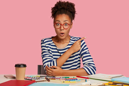 Inspired female artist draws sketch, uses sketchbook, poses at workplace in studio, points with index finger at free space against pink background. Shocked painter drinks coffee, paints with crayons Banque d'images