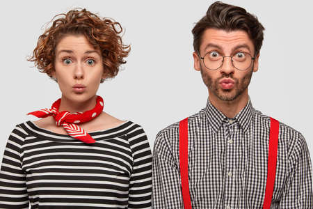 Photo of fashionable woman and man pout lips, gaze with surprised intrigued expressions, stand shoulder to shoulder, model against white background. People, emotions, style and clothes concept