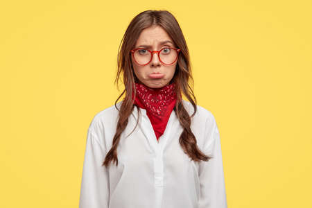 Insulted sad woman purses lower lip, being upset by terrible news, has two slightly combed plaits, wears optical glasses and white shirt, expresses negative emotions, models over yellow background