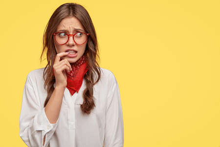 Discontent puzzled girl looks anxiously with worried expression aside, keeps fore finger near mouth, afraids of something, wears red handkerchief on neck and white shirt, copy space for advertisement