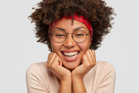 Close up shot of dark skinned girl touches cheeks, feels happy, enjoys pleasant music and good day, wears big round glasses, models over white background. Sensual feminine woman smiles broadly