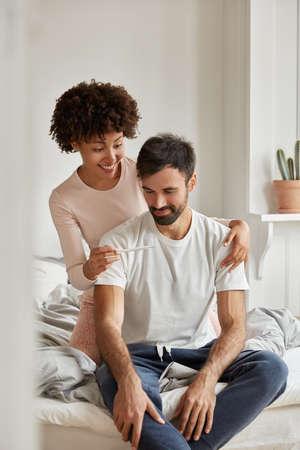 Happy multiethnic family couple look happily at pregnancy test, feel excited, celebrate good news, pose at bedroom, wears casual clothes, sit at comfortable bed during morning time. Fertility concept Stock fotó