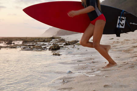 Outdoor shot of active fitness girl carries surfboard, prepares for surfing trip, stands on sandy beach near water, wears divingsuit, being free surfer, wants to demonstrate duck diving. Summer time 版權商用圖片