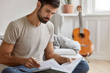 Serious young owner of entrepreneurship, studies business literature, dressed in casual t shirt, rests on bed in his room, acoustic guitar stands in background. People, home, studying, reading concept