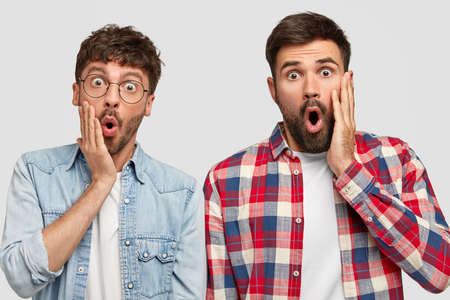 Photo of stupefied emotive two brothers find out about car accident happened with their friend, open mouthes widely, cant belive in such tragedy, wears fashionable shirt, round optical glasses Foto de archivo