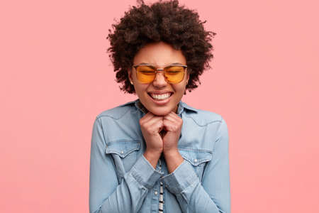 Happy black woman squints face from pleasure, smiles broadly, shows white teeth, keeps both hands under chin, wears yellow sunglasses, rejoices marriage proposal, isolated over pink background