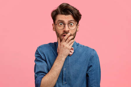 Shocked handsome young man covers mouth, has eyes popped out, stares through spectacles, wears denim shirt, models over pink background. People, unexpected reaction and surprisement concept.