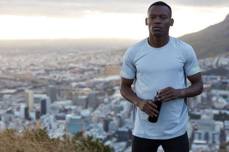 Photo of sporty muscular black man in casual t shirt, works out early in morning, carries bottle with drink, being in good physical form, stands on hill over blurred big city background, free space Reklamní fotografie
