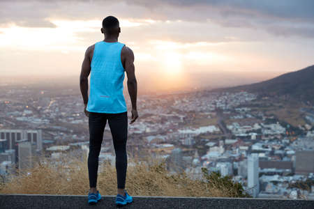 Horizontal view of attractive male dressed in casual clothes, has active run near mountains, stands back, looks attentively at beautiful sunrise at dawn, breathes fresh air, feels freedom, free space Banco de Imagens