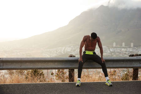 Black motivated sportsman feels exhausted after active fitness training, enjoys free lifestyle, rests after morning jog, keeps gaze down, has short hair, muscular athlete body, exercises outside