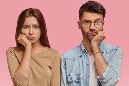 Bored girl and boy keep hand under chin, look with sadness directly at camera, feel dissatisfied, wait for something for long time, stand against pink background. People and facial expressions concept