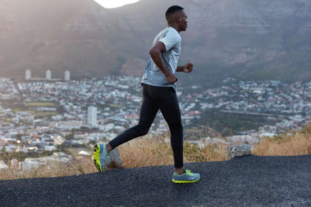 Masculine athlete person with slim healthy body dressed in sportsclothes, poses in profile, runs on high speed, participates in marathon, photographed against beautiful city view, mountain scenery 写真素材