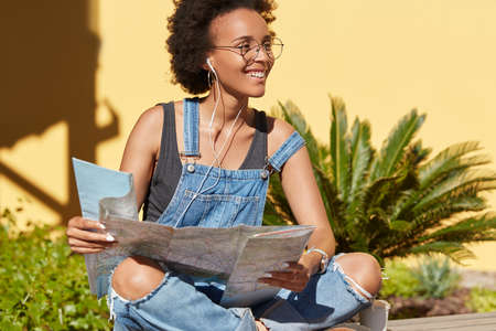 Black satisfied Afro American female traveler uses destination map for searching interesting places, looks for sightseeing in unknown place, enjoys radio broadcast in earphones, poses outdoor