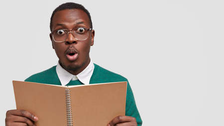 Stupefied male teenager earns notes from spiral notepad, wears big square glasses, has shocked facial expression, isolated over white background with free space for your advertising content.