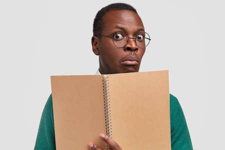 Close up shot of stupefied black student comes on lecture, holds spiral notebook for writing down information, wears optical glasses, has dark skin, shocked how much material he has to learn