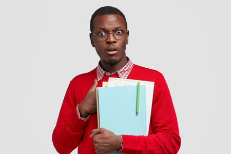Stupefied dark skinned erudite being shocked to be asked unexpected question, holds textbooks and papers with pen, dressed in fashionable red jumper, isolated over white studio wall. Surprisement 版權商用圖片
