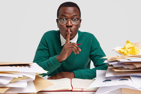 Secret African American male CEO shows silence sign, works on task recieved from boss, writes down ideas in notebook, has surprised facial expression, keeps index finger over mouth, wears glasses