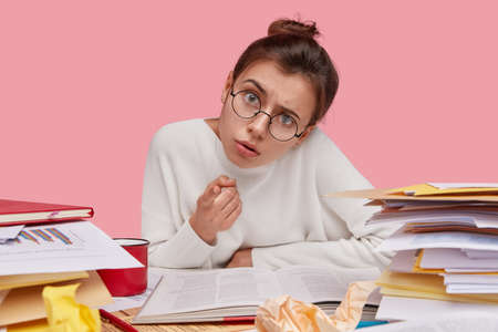 Photo of brunette woman looks scrupulously at camera, wears round spectacles, points at camera, dressed in white sweater, surrounded with documentation, sits at workplace, isolated on pink wall
