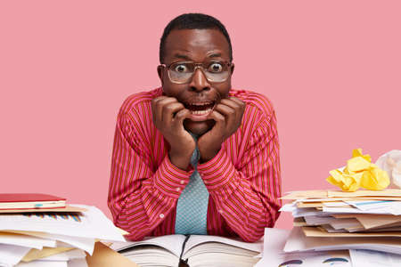Photo of neurotic stupefied male keeps both hands near mouth, stares with bugged eyes through eyewear, afraids of passing exams at university, isolated over pink background. Negative feeling concept