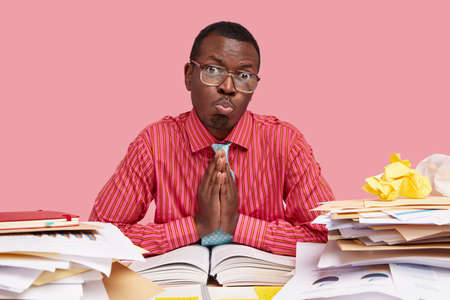 Masculine adult with black skin, has pity facial expressions, beggs for giving him one more chance to improve situation and prepare better for seminar, reads thick encyclopedia, dressed formally