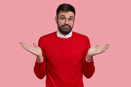 Confused unshaven man with dark bristle, spreads palms, feels uncertain, looks in displeasure, wears red sweater, models over pink studio wall. What did I do wrong. Male faces difficult question