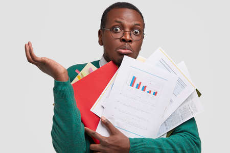Hesitant stunned black man raises hands in bewilderment, cant make decision from what to starrt, prepares business report, busy with work, isolated over white background. Student prepares for seminar