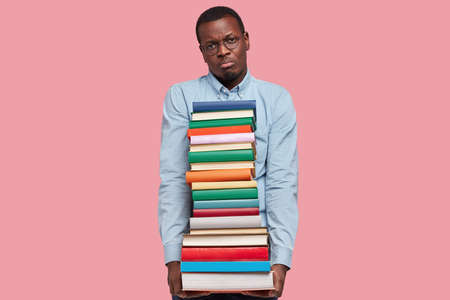 Photo of displeased dark skinned businessman holds pile of scientific books, has unhappy facial expression, weas formal shirt and spectacles, isolated over pink studio wall, expresses apathy, dislike